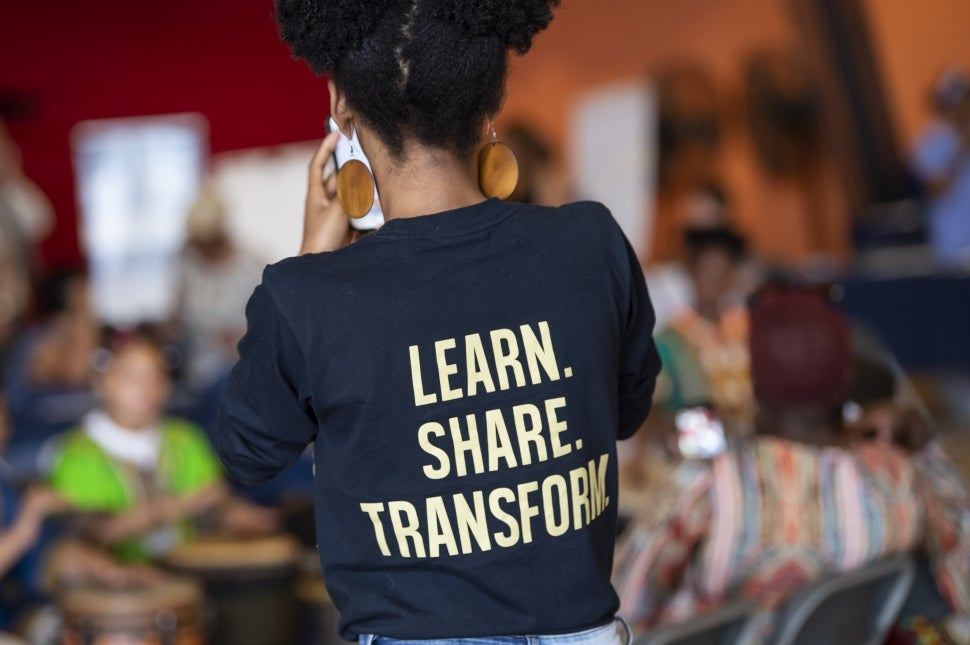 """Student with t-shirt that reads """"Learn. Share. Transform."""""""